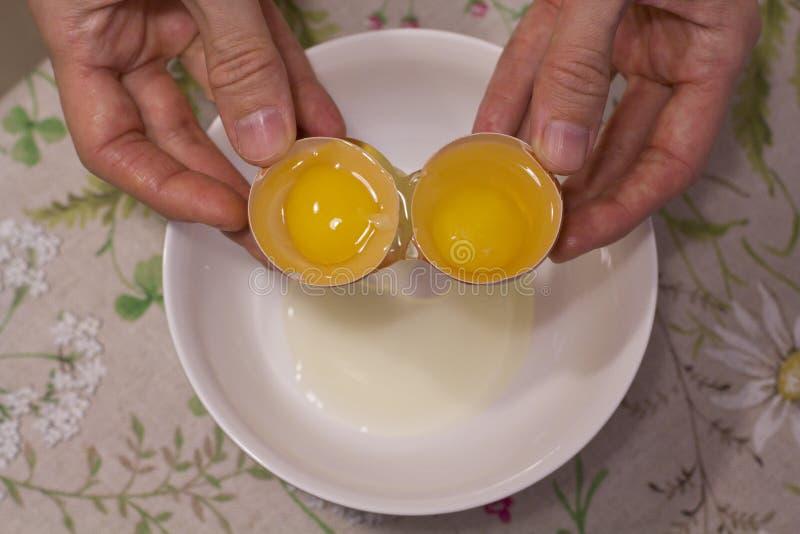 Twee dooiers in één ei 2 in 1 De handen van vrouwen openen een uniek ei met twee dooiers Het proces om eieren te openen voor het  stock foto's