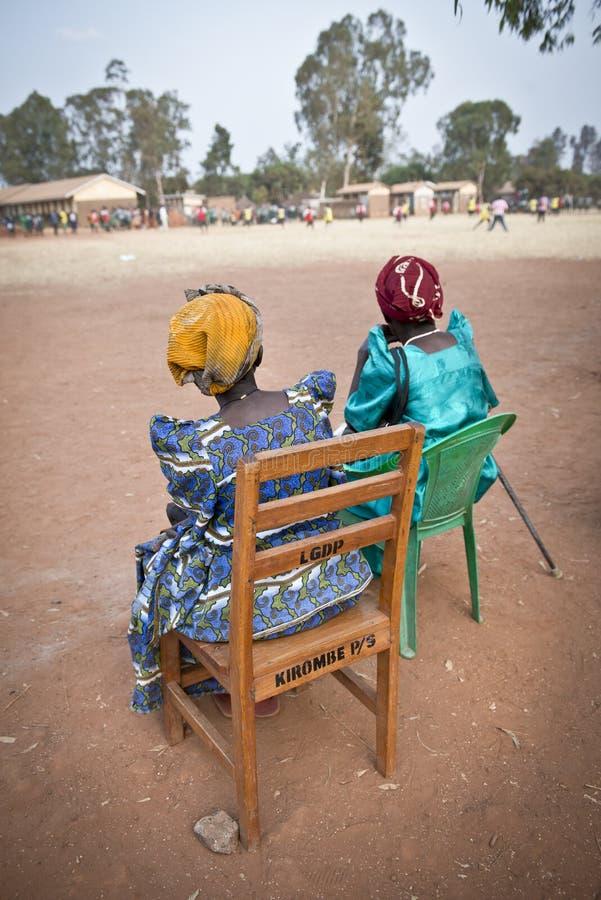 Twee dorpsdames letten op een voetbalwedstrijd op een school in Oeganda royalty-vrije stock fotografie
