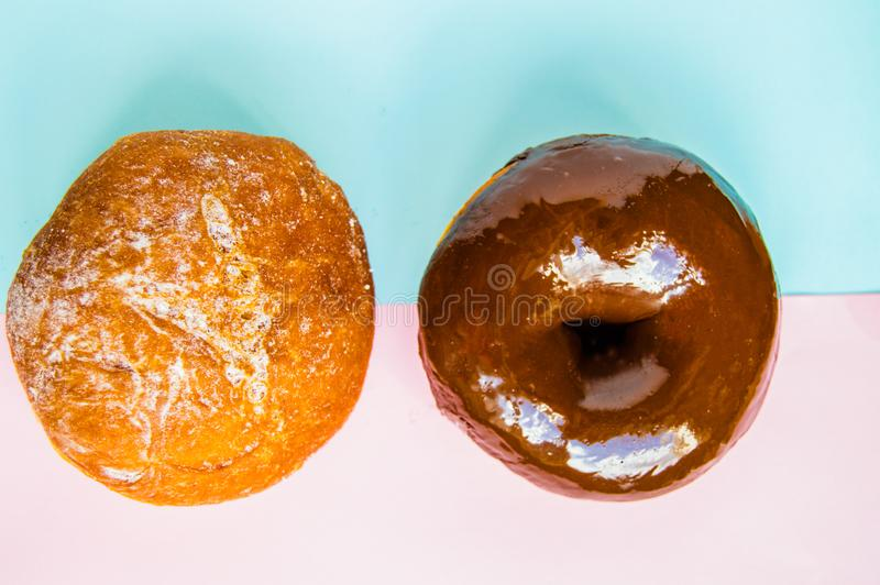 Twee doughnuts met gepoederd suiker en chocoladesuikerglazuur op pastelkleur roze en blauwe achtergrond, hoogste mening, Flatlay, stock foto