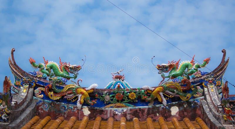 Twee draakstandbeeld op tempeldak stock foto's