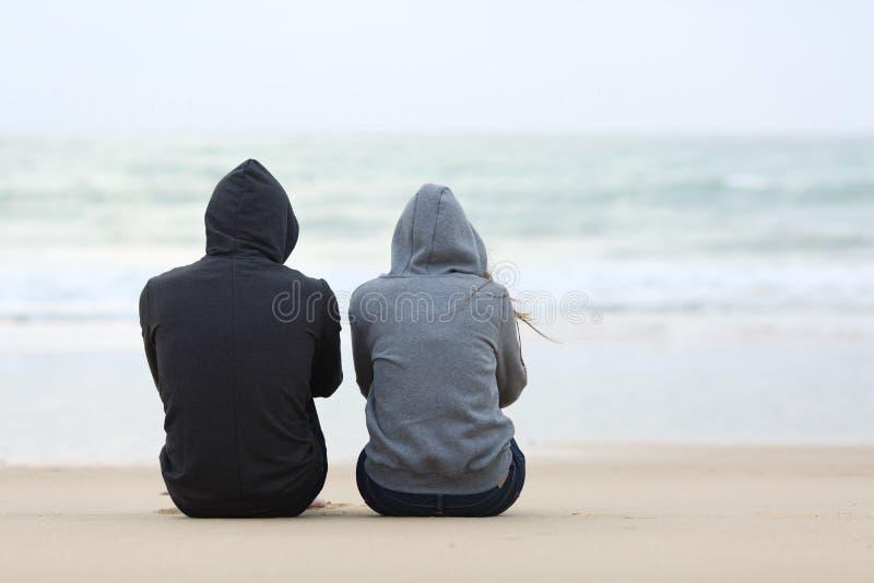 Twee droevige tieners die op het strand zitten royalty-vrije stock foto