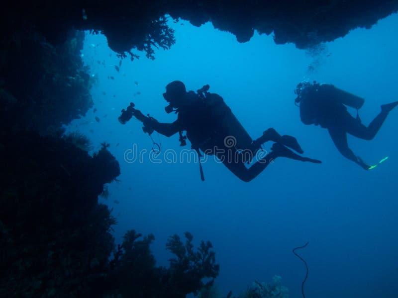 Twee duikers worden gesilhouetteerd door hol en koraal royalty-vrije stock afbeeldingen