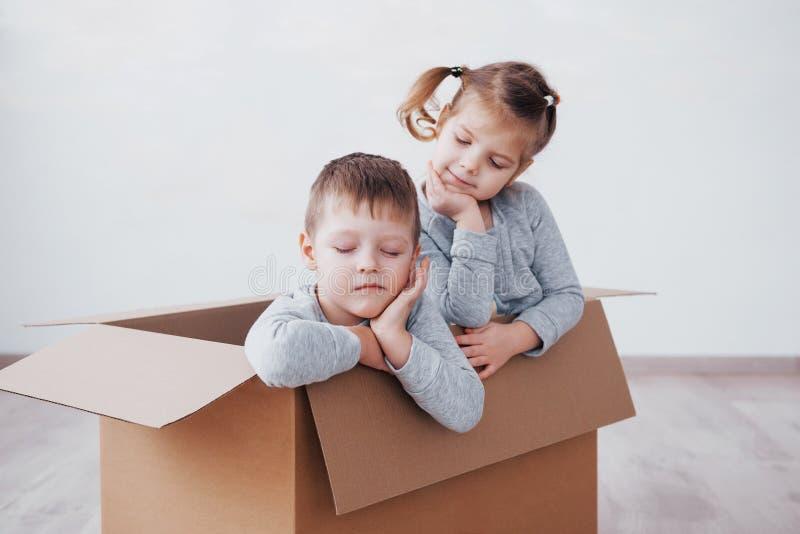 Twee een klein jonge geitjesjongen en een meisje bewogen zich enkel in een nieuw huis De foto van het concept De kinderen hebben  stock fotografie