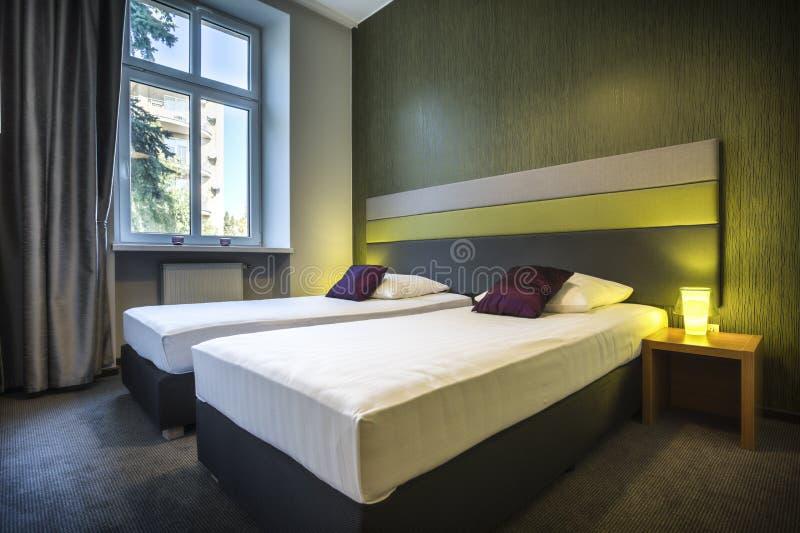 Twee eenpersoonsbedden in groene hotelruimte stock afbeeldingen