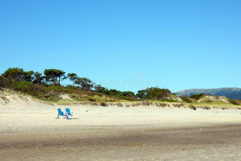 Twee eenzame stoelen op een leeg strand royalty-vrije stock afbeelding