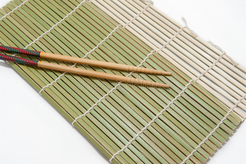 Twee eetstokjes op een achtergrond van de bamboemat stock foto