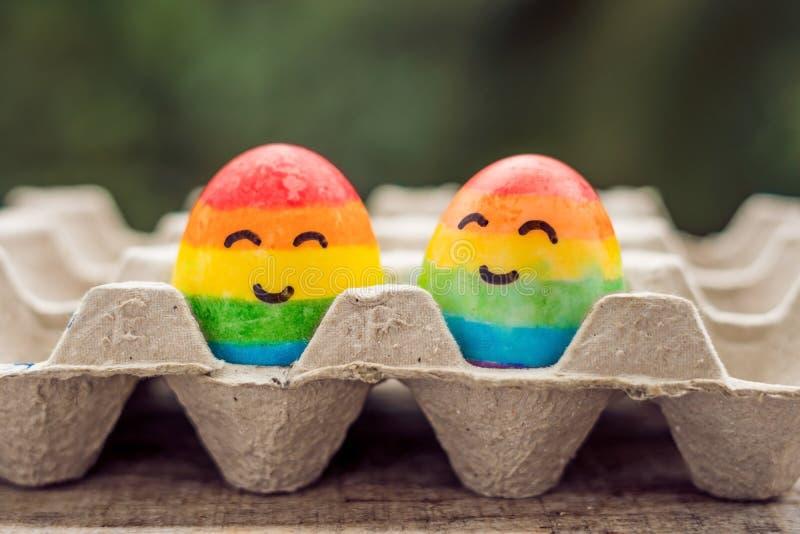 Twee eieren zijn gekleurd in de kleuren van de regenboog als vlag van homosexuelen en lesbiennes evenals paaseieren homoseksueel stock fotografie