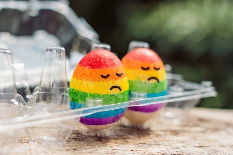 Twee eieren zijn gekleurd in de kleuren van de regenboog als vlag van homosexuelen en lesbiennes evenals paaseieren Homoseksueel  stock afbeelding
