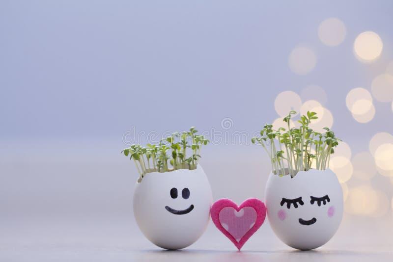 Twee eierschalenlachebekjes met tuinkersspruiten en roze hart Pasen-eierschaalplanters royalty-vrije stock foto