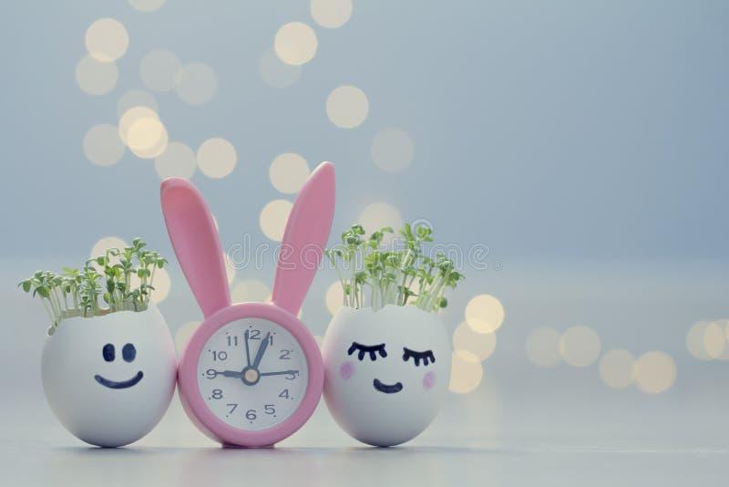 Twee eierschalenlachebekjes met tuinkersspruiten en roze konijntjeswekker Pasen-eierschaalplanters royalty-vrije stock afbeeldingen