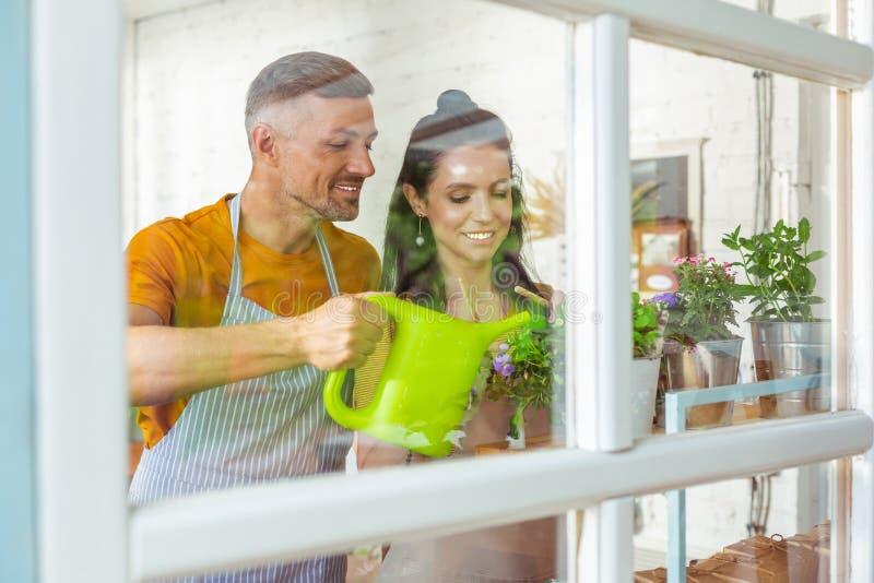Twee eigenaars die van de bloemwinkel hun installaties water geven royalty-vrije stock foto