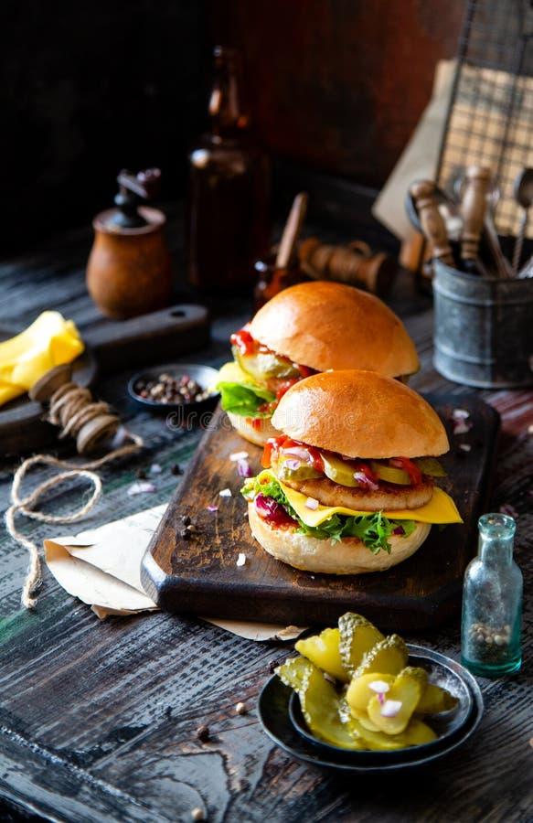 Twee eigengemaakte burgers met gebraden kip, sla, kaas, ui, ingelegde komkommers, ketchup stock fotografie