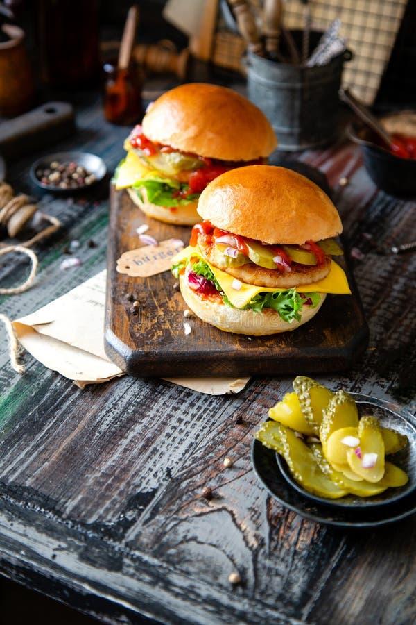 Twee eigengemaakte burgers met gebraden kip, sla, kaas, ui, ingelegde komkommers, ketchup royalty-vrije stock afbeelding