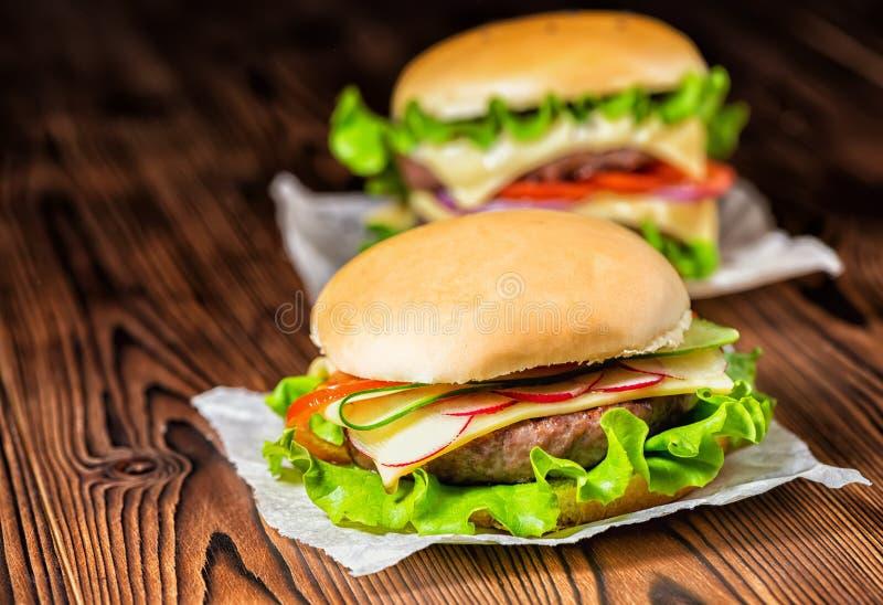 Twee eigengemaakte volledige cheeseburgers met groenten, kruiden en rundvlees stock afbeelding