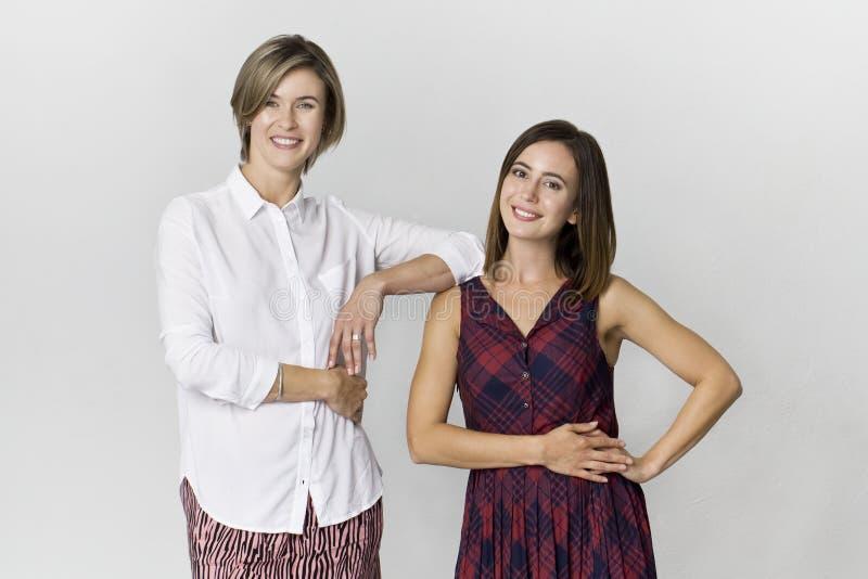 Twee elegante meisjes die pret hebben bij studioachtergrond stock fotografie