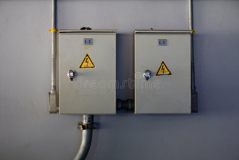 Twee elektriciteitskabinet met waarschuwingsbord op de muur royalty-vrije stock foto