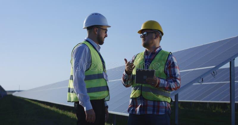 Twee elektroarbeiders die documenten op een tablet herzien royalty-vrije stock fotografie