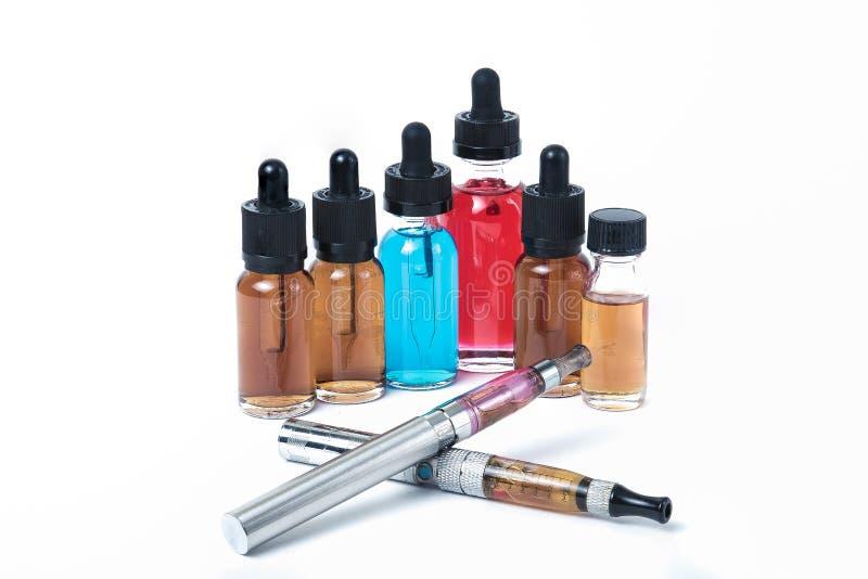 Twee elektronische sigaretten met glas e-vloeibare flessen op witte B stock foto