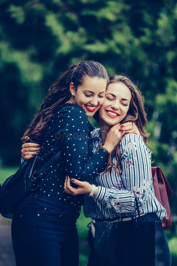 Twee emotionele gelukkige vrouwenvrienden die elkaar in het park koesteren royalty-vrije stock afbeeldingen