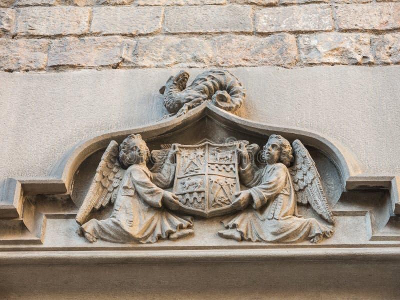 Twee engelen houden een oud schild van Barcelona, dat Vrijmetselaars- symbolen, op een draak bevat Deur van het Klooster van San  stock foto