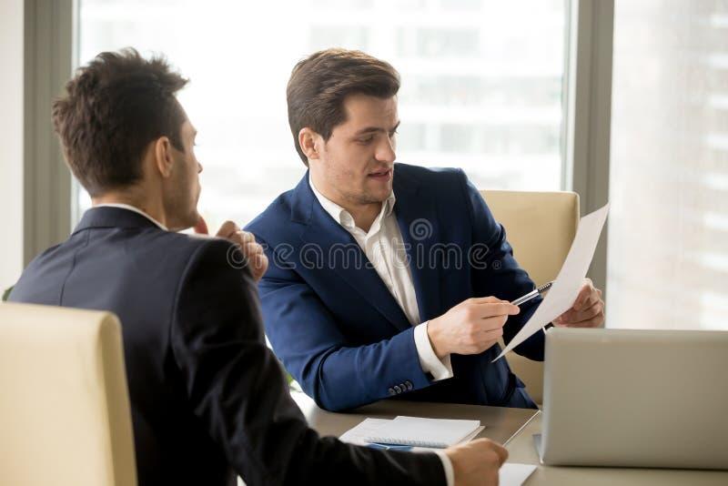 Twee ernstige partners die document, zakenlieden n bespreken royalty-vrije stock afbeeldingen