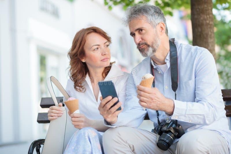 Twee ernstige rijpe toeristen die op een bank in een stad, het eten van roomijs en het spreken zitten stock afbeeldingen