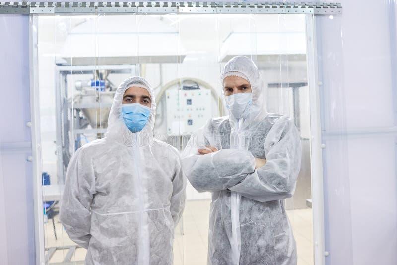 Twee fabrieksarbeiders die zich in beschermende kleren bevinden stock afbeeldingen