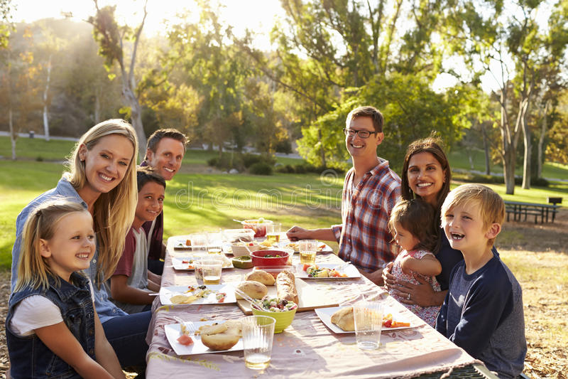 Twee families die een picknick hebben bij een lijst kijken aan camera stock foto