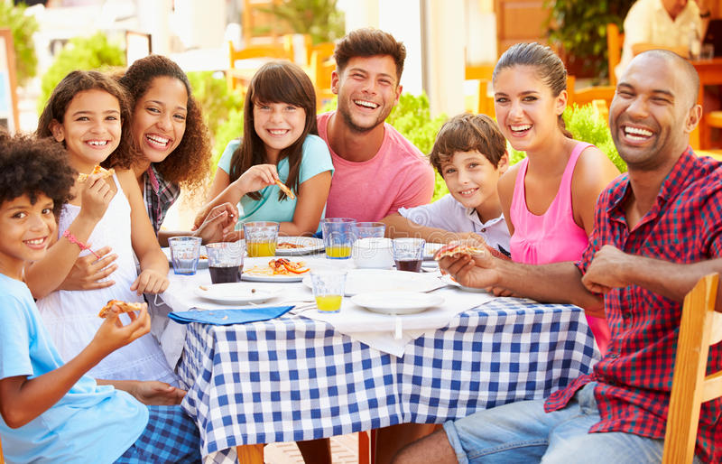 Twee Families die Maaltijd samen eten bij Openluchtrestaurant stock fotografie