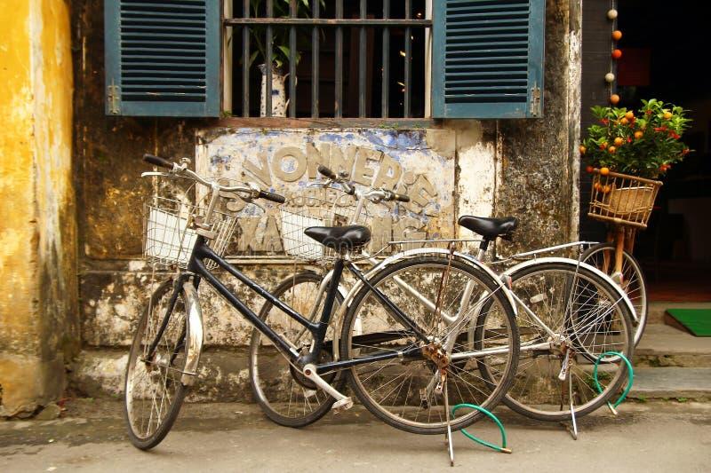Twee fietsen dichtbij aan winkel met gebarsten gele verf, houten blinden en kleine mandarijnboom op een straat van oude stad stock afbeelding