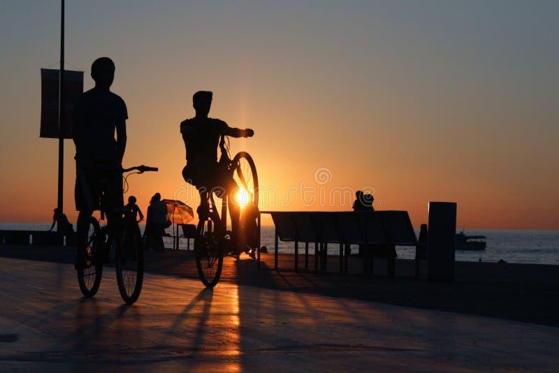 Twee fietserssilhouetten op overzeese stranddijk royalty-vrije stock afbeeldingen
