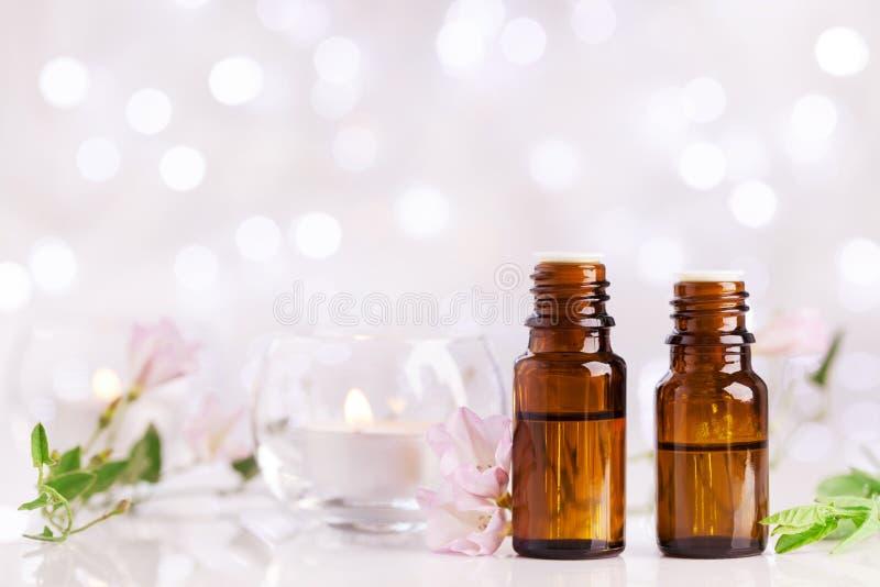 Twee flessen met etherische olie, bloemen en kaarsen op witte lijst met bokeheffect Aromatherapy kuuroord, wellness, schoonheidst royalty-vrije stock fotografie