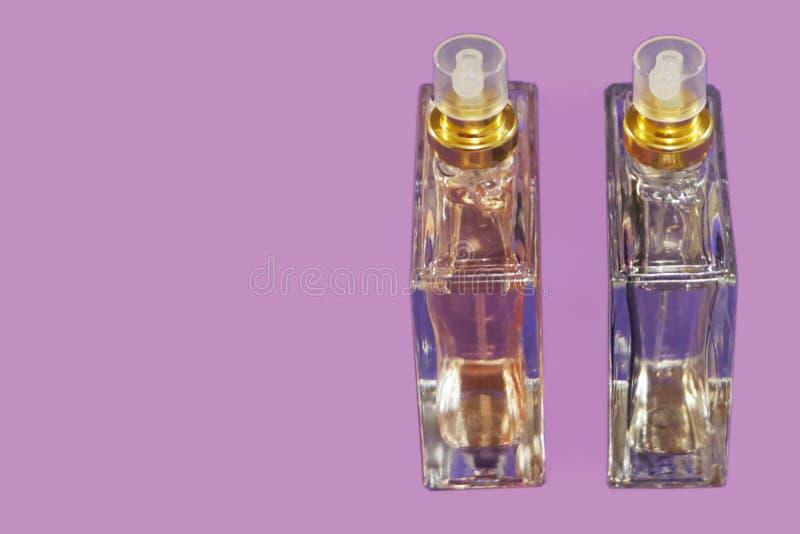 Twee flessen parfum op de lilac achtergrond met vrije exemplaarruimte voor tekst royalty-vrije stock afbeeldingen