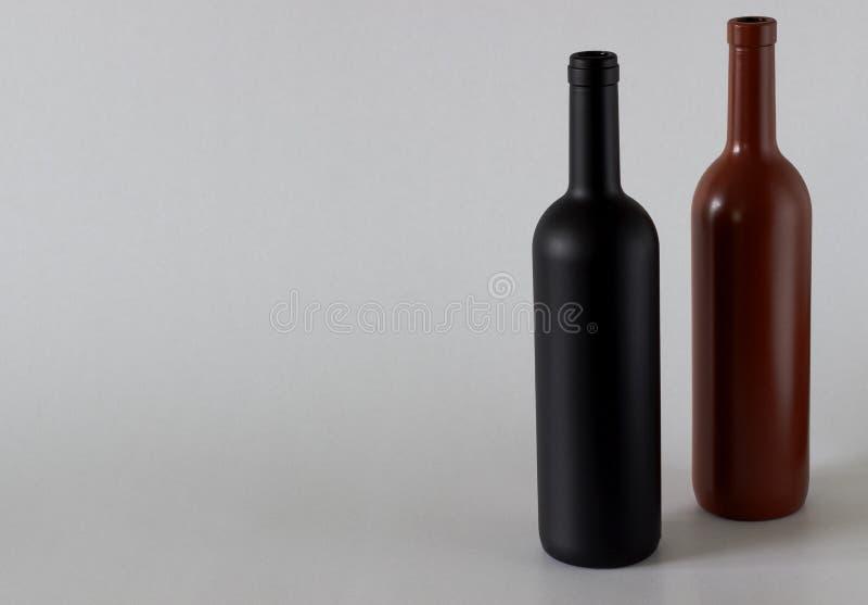 Twee flessen wijn van zwart en rood op een witte achtergrond stock afbeeldingen