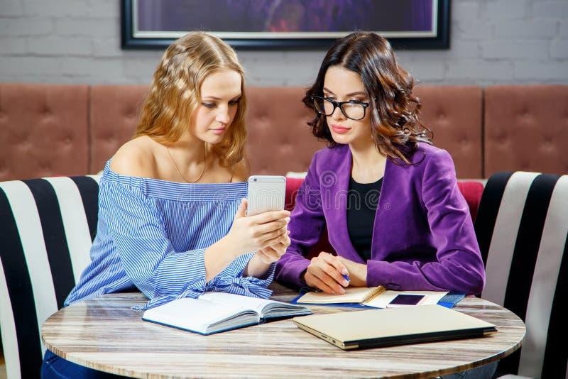 Twee freelancers bespreken nieuwe projecten terwijl het zitten in een koffie met elektronische apparaten stock fotografie