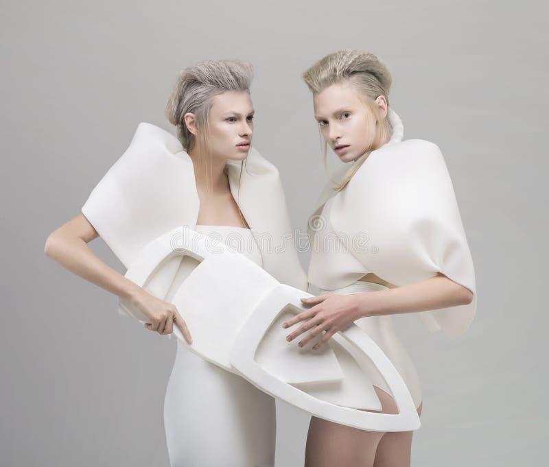 Twee futuristische blondevrouwen in witte uitrusting royalty-vrije stock foto