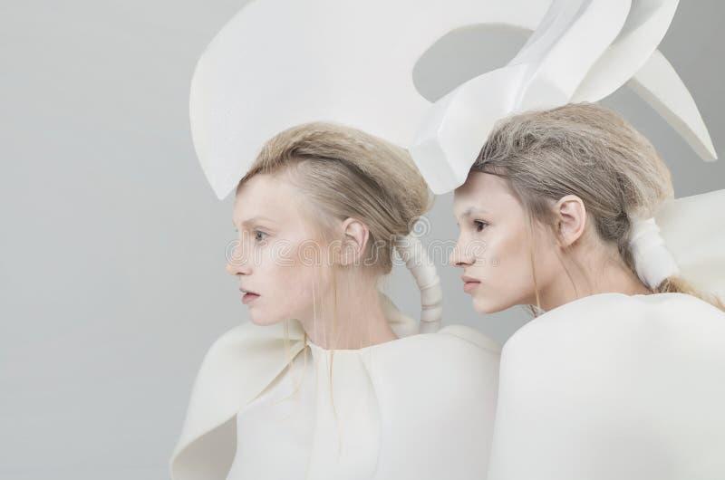 Twee futuristische blondevrouwen in witte uitrusting over w royalty-vrije stock afbeeldingen