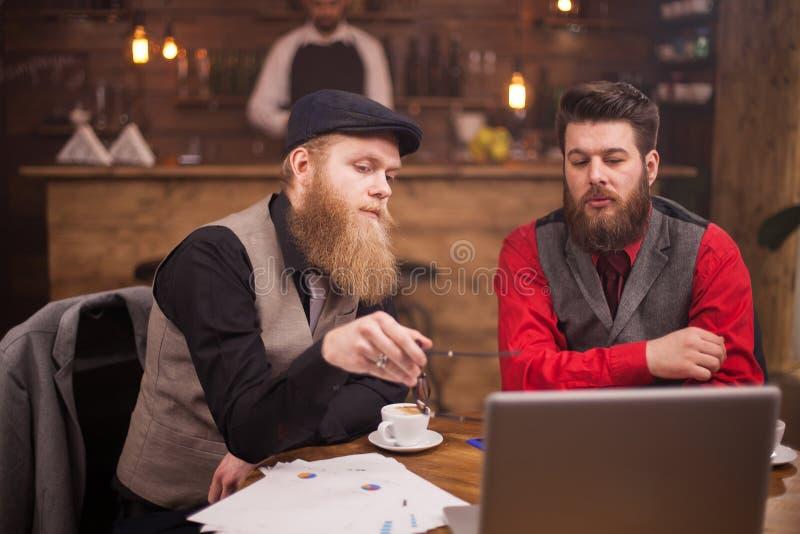 Twee gebaarde zakenlieden die informele vergadering in een uitstekende koffiewinkel hebben stock foto