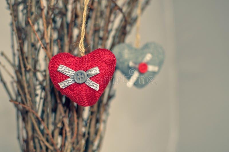 Twee gebreide harten die op een tak hangen Symbool van liefde en de dagcelebratione van Valentine Gestemde foto royalty-vrije stock afbeeldingen