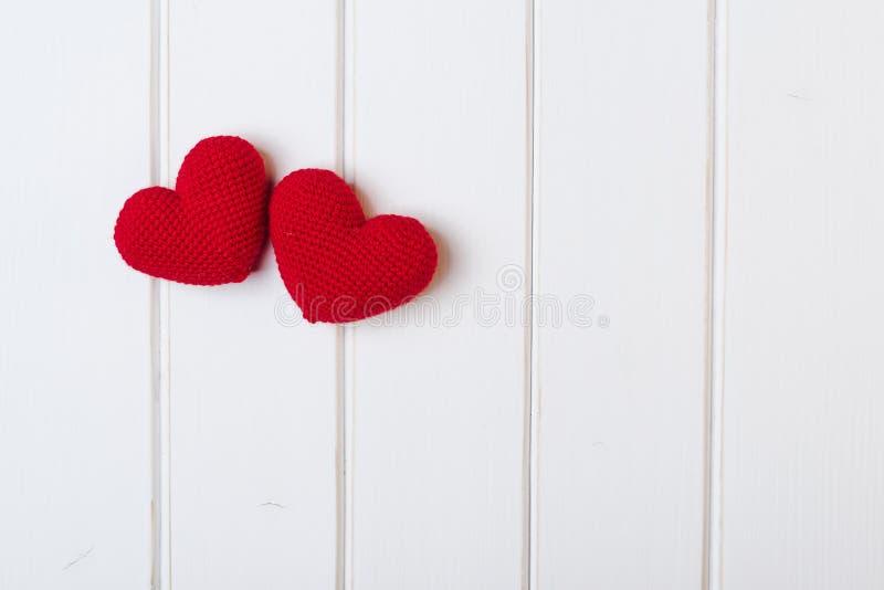 Twee gebreide harten op witte houten achtergrond De Kaarten van de valentijnskaartendag royalty-vrije stock afbeelding