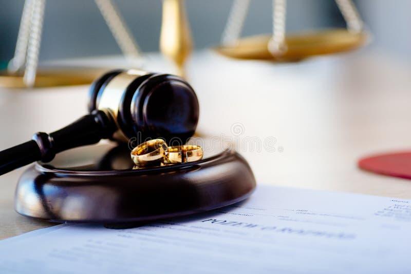 Twee gebroken gouden bruiloftringen op rechtershamer en scheidingsbesluit royalty-vrije stock afbeelding