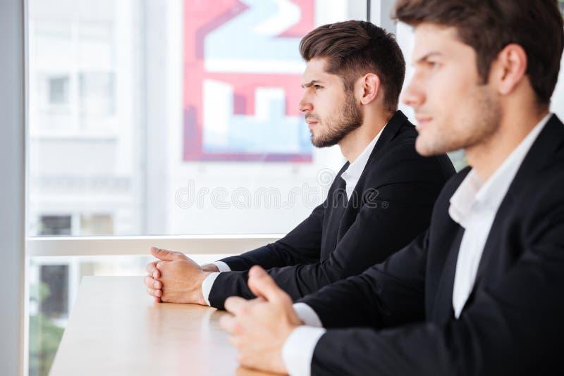 Twee geconcentreerde jonge zakenlieden die in bureau zitten stock foto