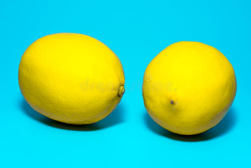 Twee geel rijp citroenenclose-up op een blauwe achtergrond, isolatie stock afbeelding