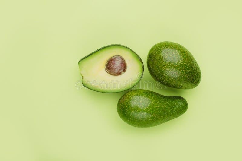 Twee gehele en halve avocado's op een groene minimalistic achtergrond, royalty-vrije stock afbeelding