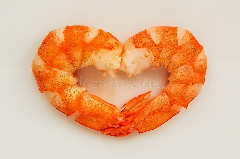 Twee gekookte gepelde koningsgarnalen in de vorm van een hart Ik houd zeevruchten van concept Het delicatesse, smakelijke en gezo stock afbeeldingen