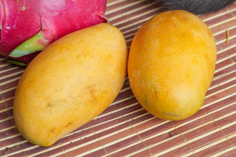 Twee gele rijpe mango's en een draakfruit stock afbeelding