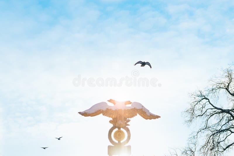 Twee-geleide adelaar op hemelachtergrond bij zonsopgang met vogels op de achtergrond Russisch embleem, gouden dubbele geleide ade royalty-vrije stock foto