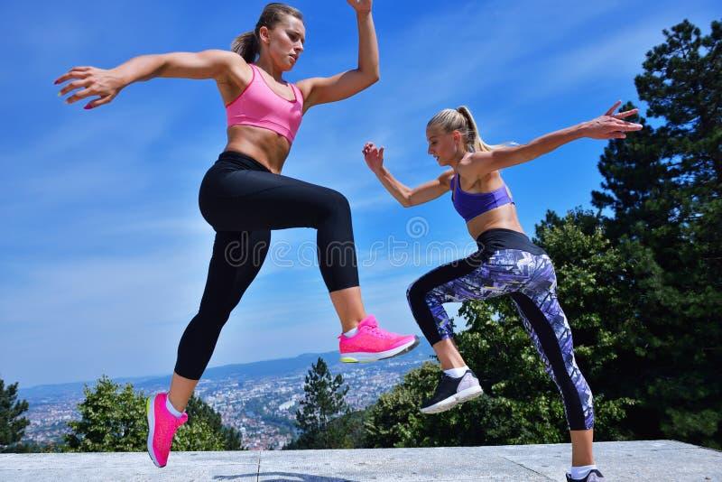 Twee geluk jonge vrouwen die over blauwe hemel springen stock afbeelding