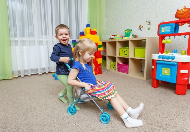 Twee gelukkig kinderenspel met stuk speelgoed wandelwagen in opvang stock fotografie