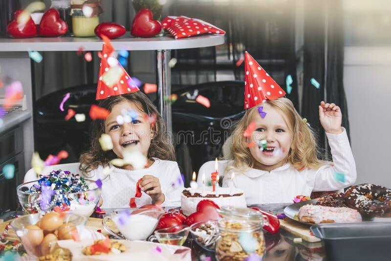 Twee gelukkig meisjeskind die een verjaardag met cake vieren bij royalty-vrije stock afbeelding